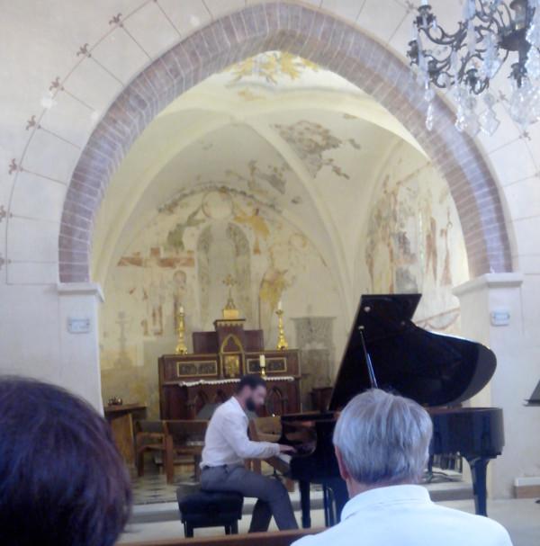 Vue de l'intérieur de l'église, on aperçoit un lustre en haut à droite, au centre il y a un pianiste (au visage flouté), et sur le devant, des spectateurices de dos.